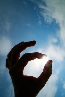 Mano agarrando el sol