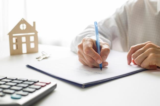 La mano de un agente de bienes raíces firma un documento de compra de vivienda. comprando una casa.