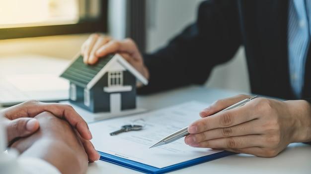 La mano del agente de bienes raíces sostiene un bolígrafo y explica el contrato comercial, el alquiler, la compra, la hipoteca, el préstamo o el seguro del hogar.