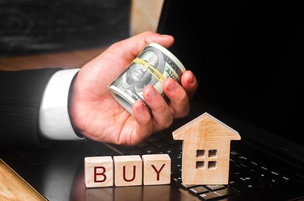 La mano del agente de bienes raíces tiene un montón de dinero detrás de la casa en miniatura.