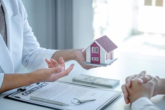Mano del agente inmobiliario explica el contrato comercial a la mujer compradora.