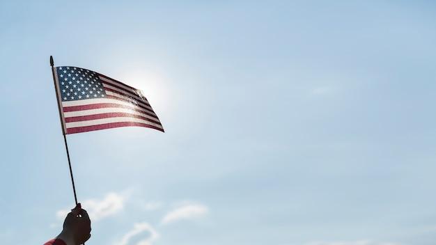 Mano agitando la bandera de estados unidos