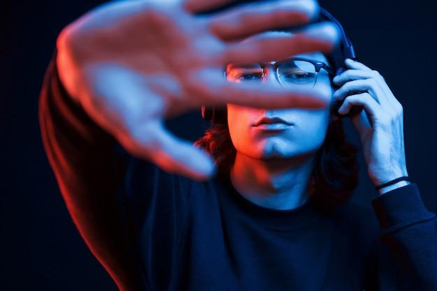 Con mano alargada. foto de estudio en estudio oscuro con luz de neón. retrato de hombre serio