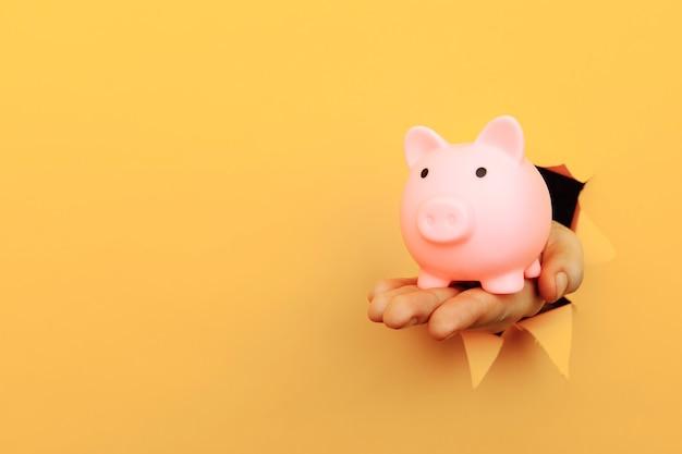 Mano con una alcancía a través de un agujero de papel amarillo concepto financiero y empresarial