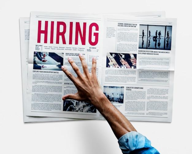 Mano alcanzando para agarrar periódico para contratar anuncio de trabajo.