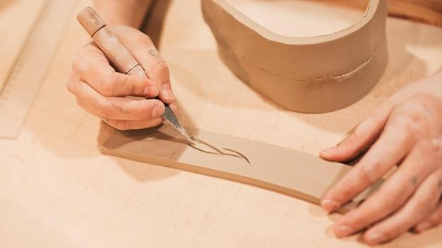 Mano de alfarero experto grabado en arcilla con herramientas afiladas