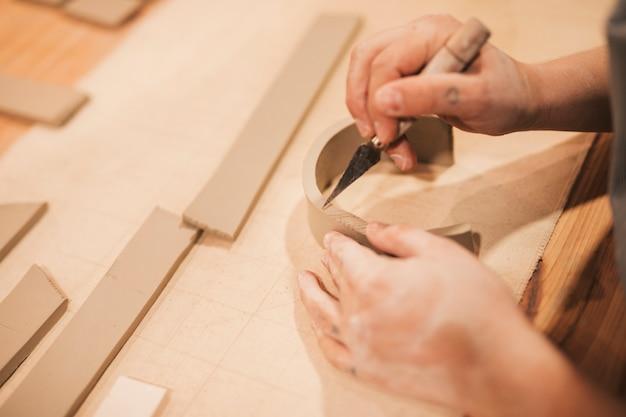 Mano de alfarero femenina grabando la arcilla con herramientas en mesa de madera