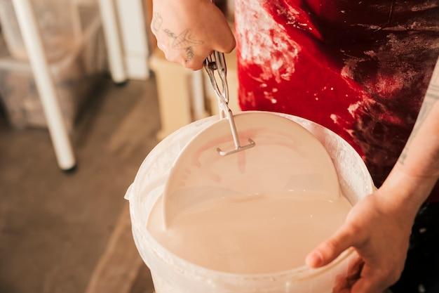 Mano del alfarero insertando el plato en el cubo de pintura con las pinzas.