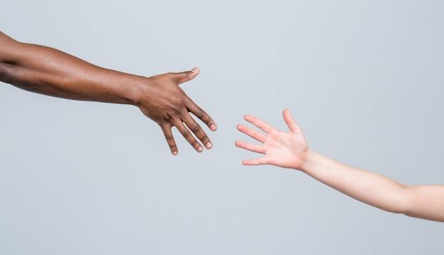 Mano amiga, rescate, personas multiétnicas. ayudar a las manos, gesto de rescate. manos humanas en blanco y negro