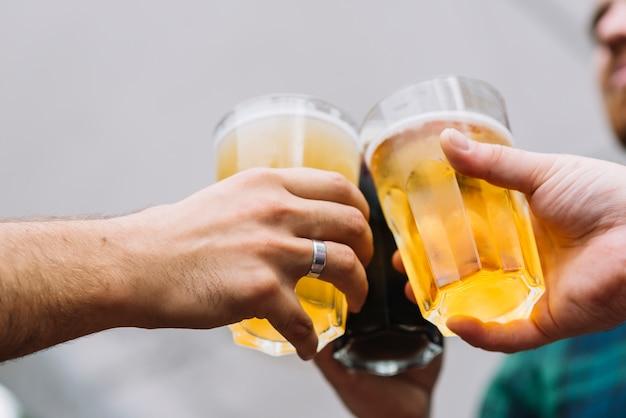 Mano de amigo brindando un vaso de cerveza