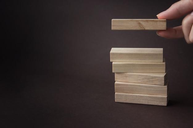 Mano amontonando y apilando un bloque de madera en la torre. concepto de negocio para el proceso de crecimiento exitoso.