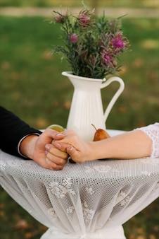 De la mano en el amor el día de la ceremonia de la boda