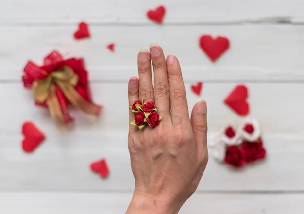 Una mano con anillo hecho de papel rosa sobre fondo blanco, romance y día de san valentín.