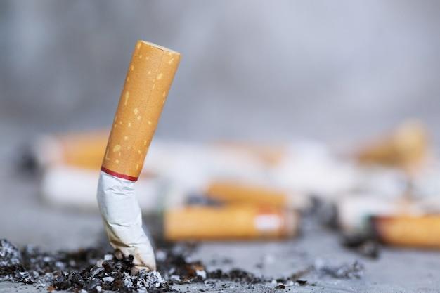 Mano apagando un cigarrillo, colilla sobre piso de concreto, cemento desnudo.