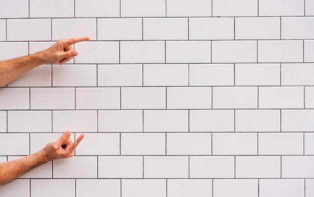 Mano apuntando a la pared de ladrillo blanco