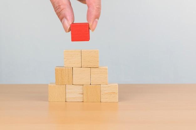Mano arreglando el apilamiento de bloques de madera como escalón. concepto de trayectoria profesional de escalera para el proceso de éxito del crecimiento empresarial