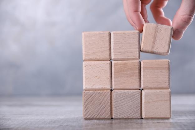 Mano arreglando el apilamiento de bloques de madera como escalón en la mesa de madera. concepto de negocio para el proceso de éxito de crecimiento. copia espacio