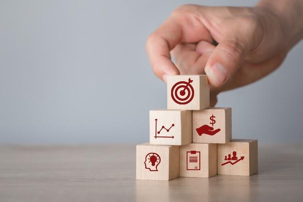 Mano arreglando el apilamiento de bloques de madera con flecha de icono y negocios, apuntando al concepto de negocio