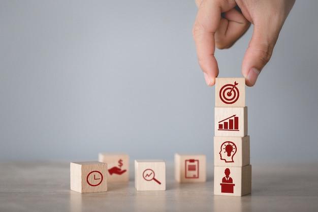 Mano arreglando el apilamiento de bloques de madera con flecha de icono y negocios, apuntando al concepto de negocio.