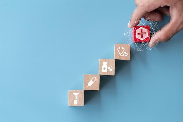 Mano arreglando apilamiento de bloques de madera con icono de salud médica