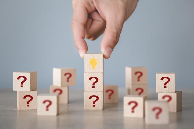Mano arreglando el apilamiento de bloques de madera con icono de signo de interrogación y lámpara, pensando con el concepto de signo de interrogación.
