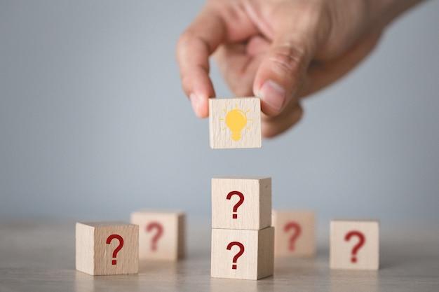Mano arreglando el apilamiento de bloques de madera con el icono de signo de interrogación y lámpara, pensando con el concepto de signo de interrogación.