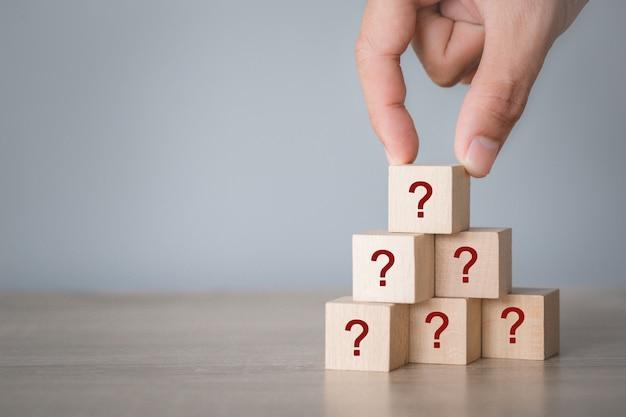 Mano arreglando el apilamiento de bloques de madera con el icono de signo de interrogación, pensando con el concepto de signo de interrogación.