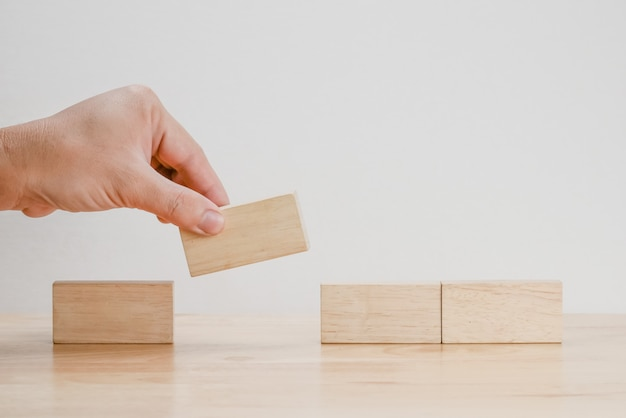 Mano arreglando bloque de madera