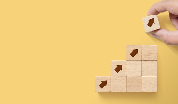 Mano arreglando bloques de madera con flechas sobre fondo amarillo
