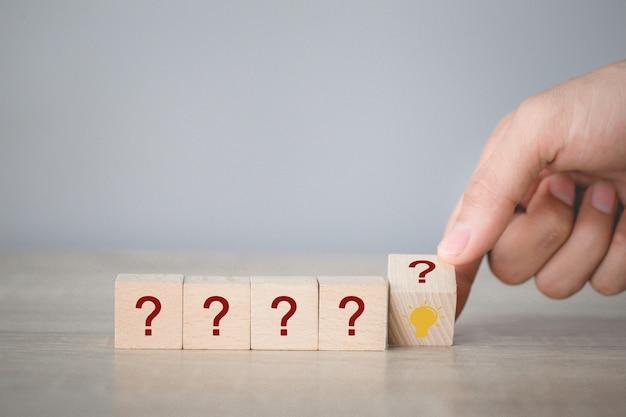 Mano arreglando voltea apilamiento de bloque de madera con icono de signo de interrogación y lámpara, pensando con el concepto de signo de interrogación.