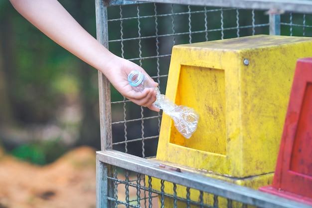 Mano arroja una botella de plástico en el contenedor