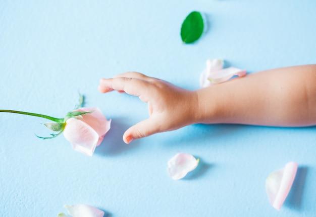 Mano de arte de moda de un niño pequeño con flores sobre fondo azul