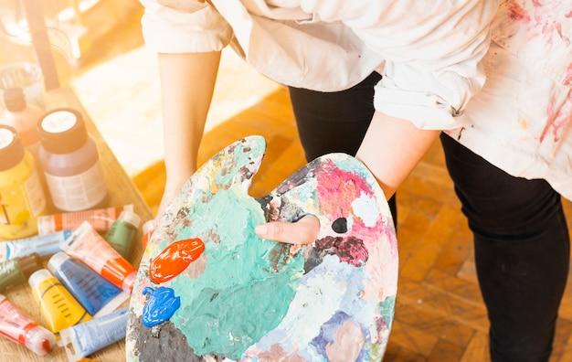 Mano de artista femenina sosteniendo la paleta de pintura desordenada en el taller