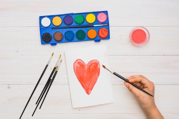 La mano del artista que sostiene el pincel en la mano dibujada forma de corazón pintura sobre superficie de madera