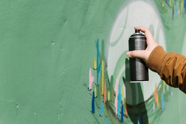 Mano del artista rociando en la pared de graffiti con aerosol