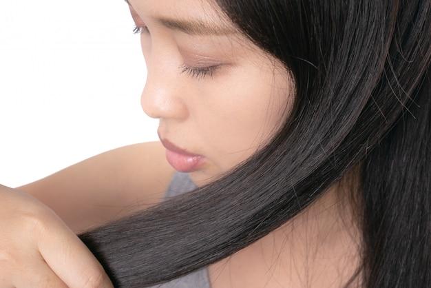Mano asiática de las mujeres adultas que sostiene su pelo largo con mirar las puntas abiertas dañadas del pelo.