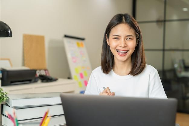 La mano asiática sonriente de la mujer que sostiene el libro y la pluma con el texto de la nota forman el aprendizaje en la computadora portátil en casa.