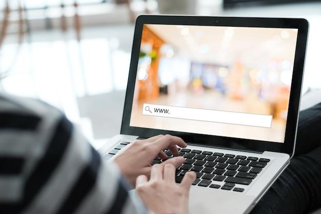 Mano atando la computadora labtop con www. en la barra de búsqueda sobre fondo borroso de la tienda en la pantalla