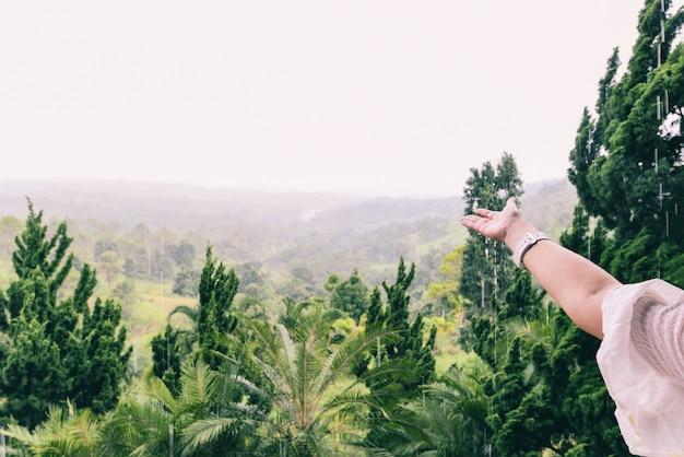 Mano atrapando gotas de lluvia sobre fondo verde de la naturaleza