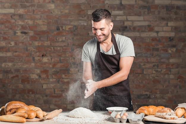 La mano de baker aplaudiendo una harina sobre la masa amasada en la mesa