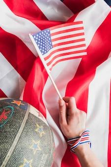 Mano con bandera de estados unidos y baloncesto.