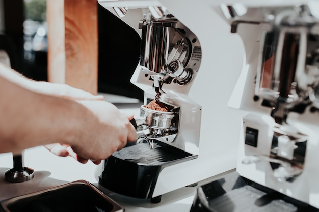 Mano de un barista haciendo café con una máquina de café en un café.