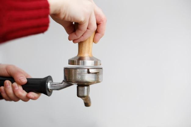 La mano del barista de primer plano aplasta el café molido con la manipulación en el soporte de la máquina de café