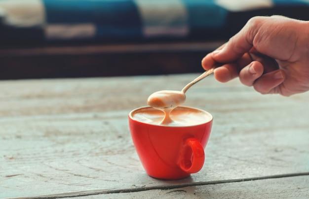 Mano de barista sosteniendo una cuchara con una suave crema de café con leche con patrón en una taza de cerámica roja sobre la mesa de madera blanca.