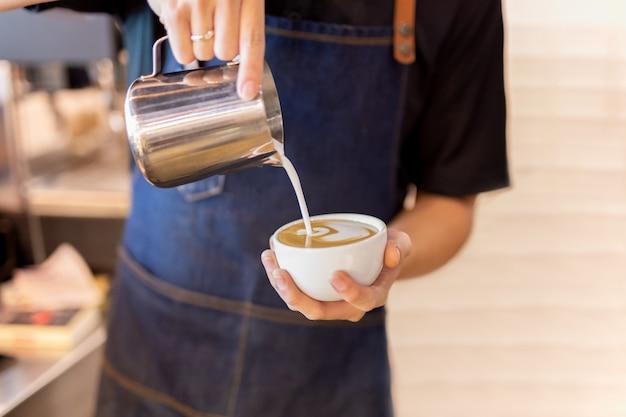 La mano de barista vierte la leche que hace el café del arte del latte en el café.