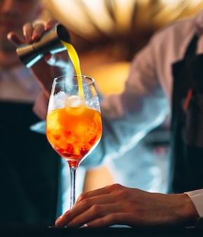 Mano de barman revolviendo un cóctel de verano de naranja fresca y dulce con una cuchara en la barra del bar
