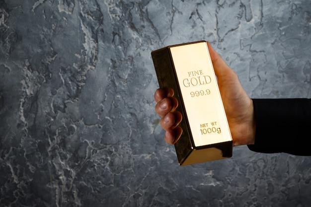 De la mano con una barra de oro