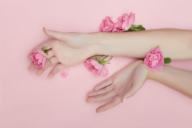Mano de belleza de una mujer con flores rojas se encuentra en la mesa, papel rosa