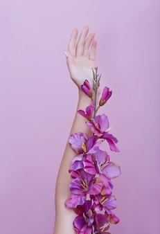 Mano de belleza de una mujer con flores rojas se encuentra en rosa