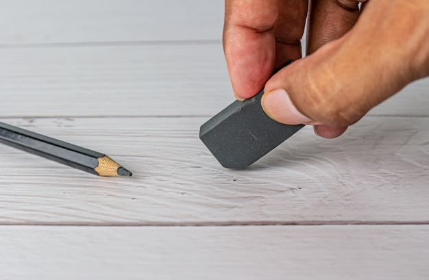 Mano con borrador negro y lápiz sobre mesa blanca